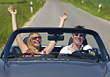 Couple Driving In Convertible, Her Arms Raised stock photo
