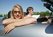 Couple Driving Convertible, She Leaning Over Door stock photography