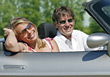 Couple Driving Convertible, She Resting Head In Hand stock photo