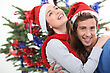 Couple Hugging In Front Of A Christmas Tree stock photo