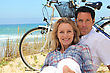 Couple On The Beach With Bikes stock photography