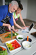 Couple Preparing Vegetables And Looking At A Laptop