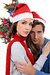 Couple In Santa Hats In Front Of A Christmas Tree stock photo