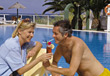 Couple sharing a tropical drink by a resort swimming pool stock image