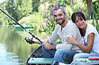 Couple Sitting In A Boat Fishing