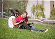 Couple Sitting in Grass Reading stock photography