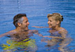 Couple smiling at each other while floating in the pool stock photo