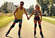 Couple On Street In Inline Skates Holding Hands stock photography