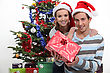 Couple Wearing Festive Hats Stood By Christmas Tree stock photo