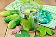 Cucumbers In A Glass Jar And On The Table, Garlic, Tarragon, Dill, Cover With Napkin, Leaves On A Wooden Boards Background stock photo