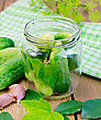 Cucumbers In A Glass Jar And On The Table, Garlic, Tarragon, Dill, Napkin, Cherries And Currants Leaves On The Background Of Wooden Boards stock photo