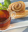 Cup Of Tea With Cinnamon Danish Bun On Textile Background