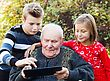 Curious Grandfather Learning From His Grandchildren How To Use A Tablet stock photo