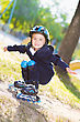 Cute Boy Rollerblading Near The Playground With Spaced Apart Arms stock photo