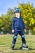 Cute Cheerful Boy Posing On Roller Skates Outdoors stock photo