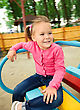 Cute Cheerful Little Girl Is Riding On Merry-go-round, Background Blurred With Motion stock photo
