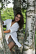 Cute Girl In A White Shirt Standing Near The Birches stock photo