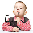 Cute Little Child Is Biting Glasses While Sitting At Table stock photo