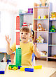 Cute Little Girl Excited Using Building Bricks In Preschool stock photo