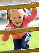 Small Cute Little Girl Is Climbing Up On Ladder In Playground stock photo