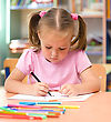 Playful Cute Little Girl Is Drawing With Felt-tip Pen In Preschool stock photo