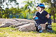 Cute Little Skater Boy Resting On The Stone In The Park stock photo