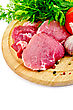 Cuts Of Meat, Garlic, Tomatoes, Parsley, Dill On A Round Wooden Board stock photo