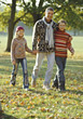 Dad and Kids Walking in Park stock photography