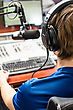 Dj Working In Front Of A Microphone On The Radio, From The Back stock photography