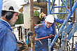 Geological Drilling Crewman Tightens Pipe On Drillstring stock image