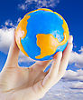 Fluffy Earth W In Hand Against The Blue Sky stock photo