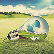 Eco Energy Concept. Light Bulb With Green World Inside Over Natural Backgrounds With Shallow DOF