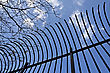 Edge Of An Old Bended Metal Bars Railing Against Blue Sky stock photo