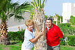 Elderly Couple Embrace Each Other Near The Palm-tree On Tropical Resort