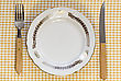 Empty Dinner Plate With Fork And Knife On Tablecloth stock photo