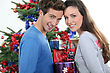 Romance Excited Young Couple Stood By The Christmas Tree stock photography