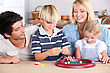 Family Playing Game At Kitchen Table stock image