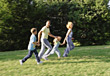 Family Running Across Lawn stock image