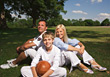 Family Sitting in Grass Smiling Happy stock photo
