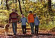 Family Walking With Dog Through Autumn Park stock photo