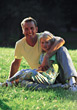 Father and Daughter Sitting on Grass stock photo