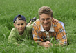 Father and Son Laying in Grass stock image