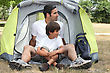 Father And Son Sitting Outside A Tent stock photo