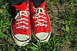 Feet In Red Sneakers In Green Grass stock photography