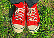Feet In Red Sneakers In Green Grass stock image