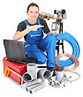 Female Plumber With Tools Of The Trade, Laptop Computer And Smartphone stock photo