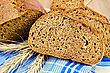 Few Slices Of Rye Bread, Three Rye Spikelets On A Blue Napkin Against A Wooden Board stock photography