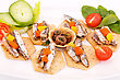 Fish And Peppers On Crackers With Vegetables On White Plate stock photo