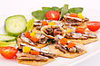 Fish And Peppers On Crackers With Vegetables On White Plate