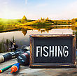 Fishing Tackle And A Blackboard On A Background Of Lake At Sunset stock image